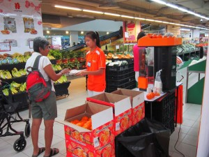 Customer trying Kinnow juice at Sheng Siong supermarket