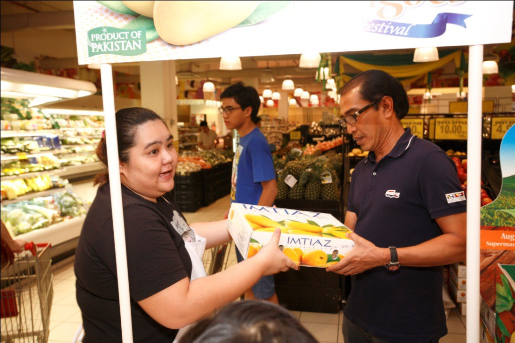 A Malaysian consumer likes the taste of Pakistani mangoes so much he buys a whole box; at the Pakistan King of Mangoes Festival sampling booth at the Village Grocer supermarket