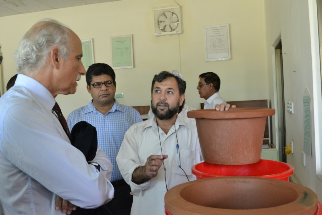 Jehangir Shah, Deputy QM PCSIR, demonstrating the use of the water filtration sytem developed by PCSIR being fed in the flood affected areas.