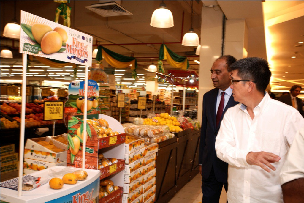 Kit Chan of UNIDO showing Syed Hassan Raza, the Pakistan High Commissioner to Malaysia the sampling booth and advertising displays for the Pakistan King of Mangoes Festival at the Village Grocer s