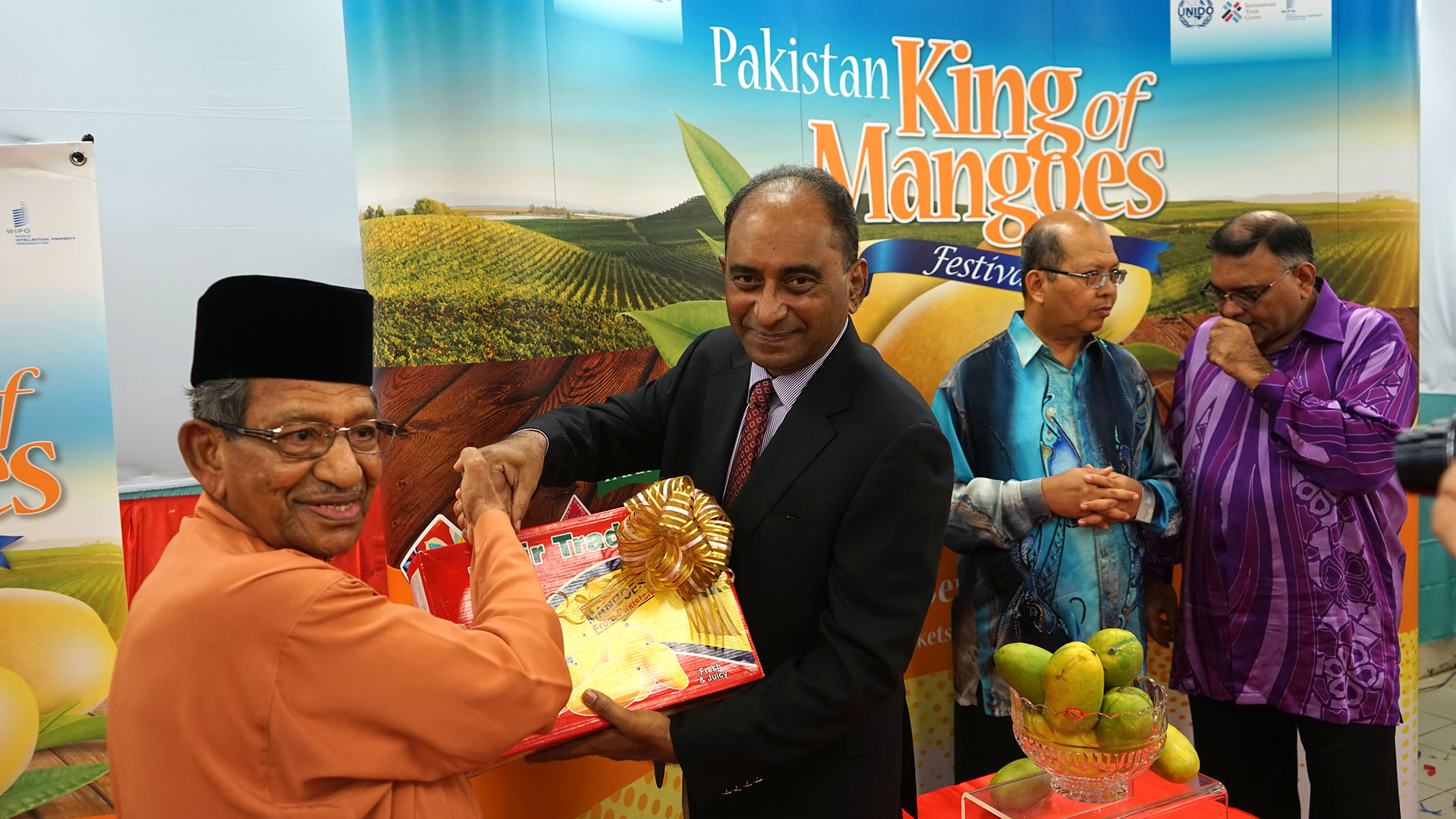 (L-R) Tan Sri Yusoff Latif receiving a box of Pakistan mangoes from Syed Hassan Raza while Dato' Seri Farizan and Dato' Abdul Rafique engage in conversation.