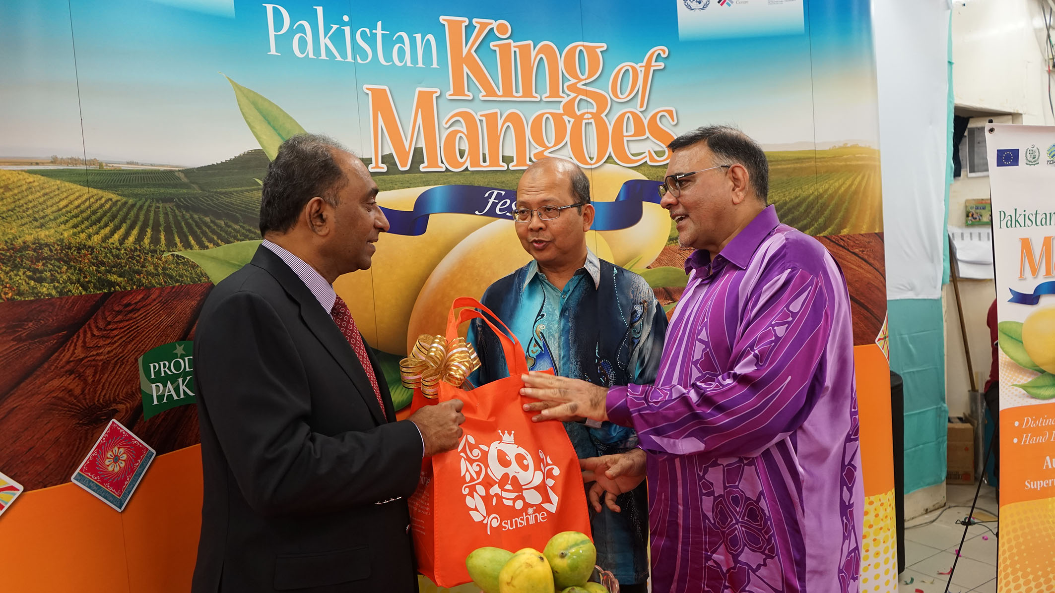 Syed Hassan Raza (L) receiving a bag of Penang delicacies from Dato' Abdul Rafique (R) while Dato' Seri Farizan (middle) looks on.